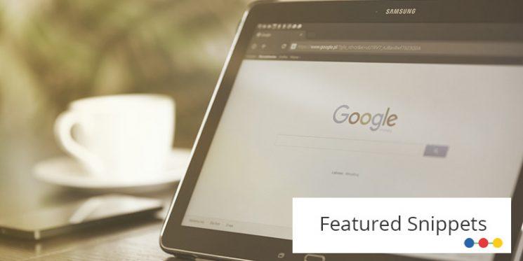 Blick auf das Display eines Tablets, im Hintergrund sind Kaffeetasse und Smartphone