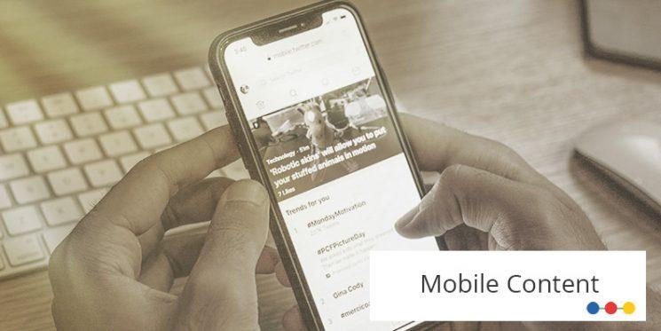 Mann hält Smartphone in den Händen am Arbeitsplatz, sodass das Display sichtbar ist